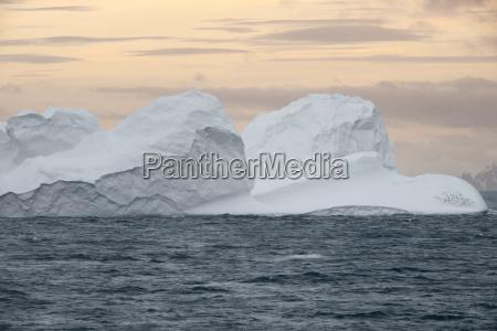 large iceberg floating at sunset in