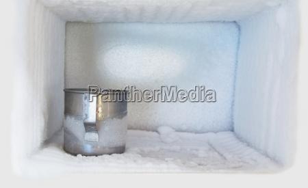 edelstahl trinkwasserglas im gefrierschrank eines kuehlschranks