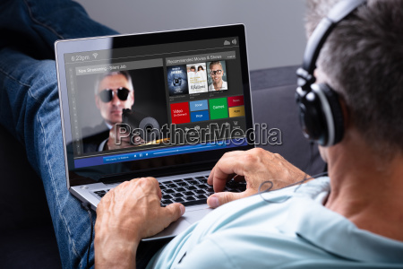 man schaut film auf laptop