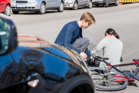 hilfreicher junger mann der einer verletzten