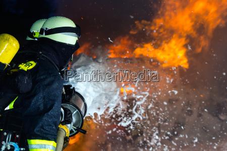 feuerwehr feuerwehrleute loeschen eine grosse flamme