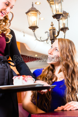 waitress serving cake in pastry shop