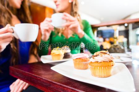 frauen essen muffins beim trinken