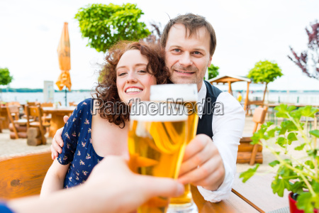 couple toasting toward friends in beer