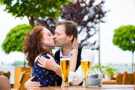 man kissing woman in beer garden
