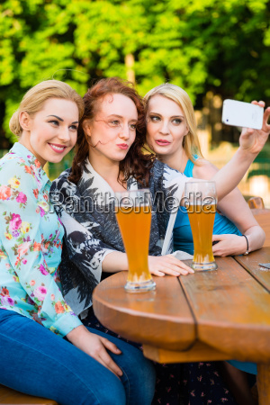 friends taking selfie with smartphone in