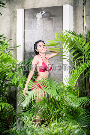 asian woman using shower in tropical