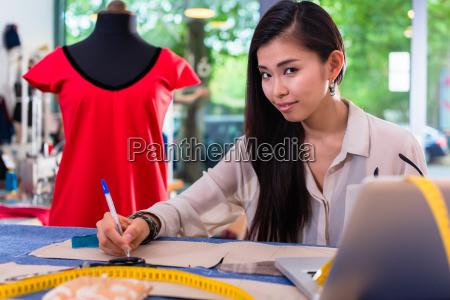 asian fashion designer preparing drafts for