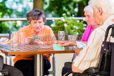 gruppe von senioren spielen brettspiel auf