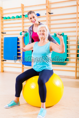 senior woman with trainer at fitness