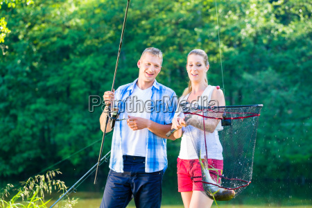 couple sport fishing bragging with fish