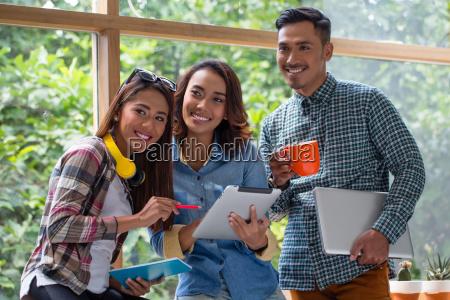 drei froehliche junge mitarbeiter arbeiten gemeinsam