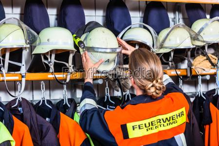 feuerwehrfrau in der umkleidekabine mit helm