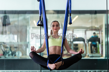 beautiful fit woman meditating while hanging