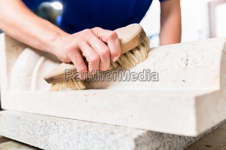 steinmetze gebuerstet steinstaub vom werkstueck