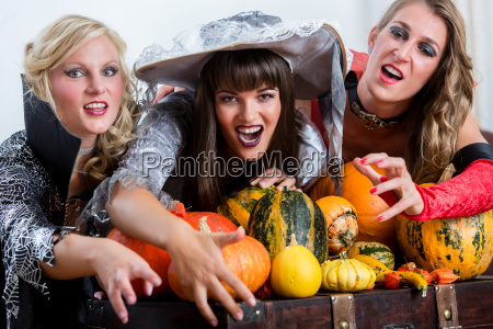 four cheerful women celebrating halloween together