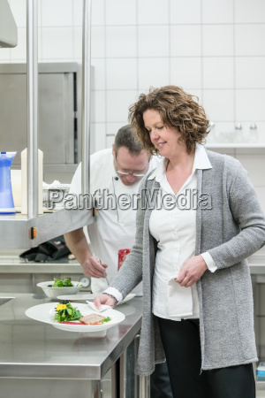 service woman taking food from chef