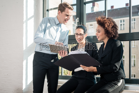 three young cheerful employees smiling in