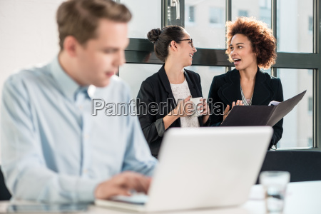 two young cheerful female employees talking