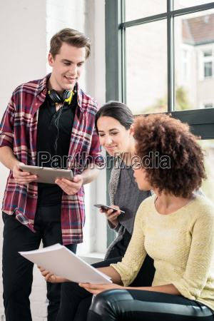 three young employees using modern devices