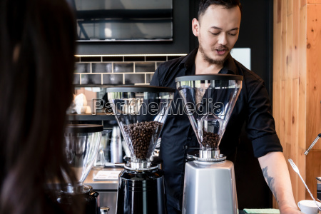 young barista preparing coffee from fresh