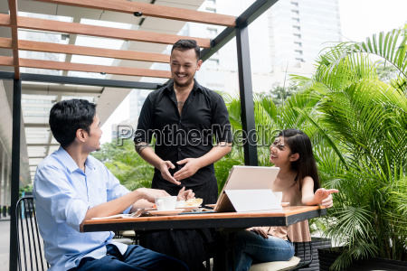 friendly young waiter talking with the