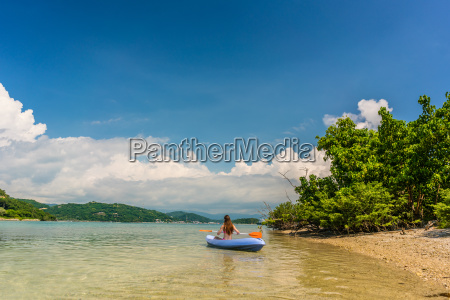 young woman paddling during vacation in