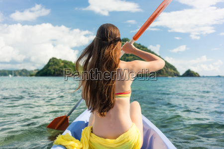 young woman paddling a canoe on