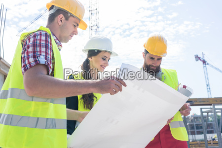 experienced architect analyzing a blueprint on