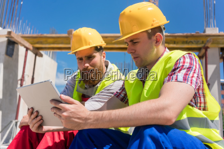 two workers reading online information or
