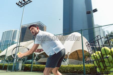 junger mann spielt tennis im freien