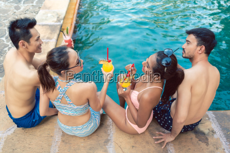 two young couples drinking cocktails while