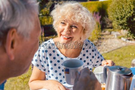 happy elderly couple eating breakfast in
