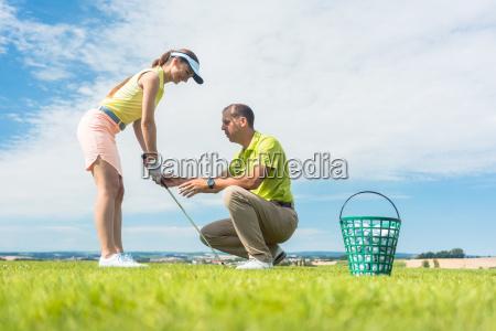junge frau die den golfschwung trainiert