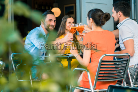 cheerful friends toasting with a refreshing