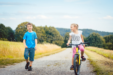 boy and girl walking and riding