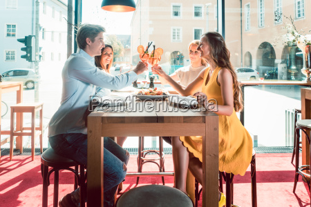 young friends toasting with cocktails before