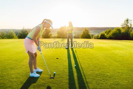 golfspielerin bereit den ball in den