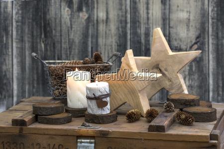 rustikales weihnachtsstillleben mit kerzen auf alten