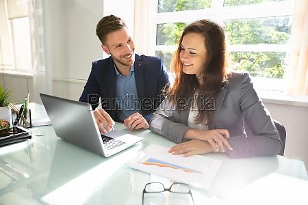 glueckliche geschaeftsleute arbeiten am laptop
