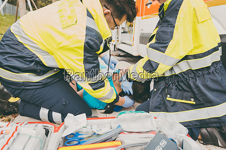 paramedics performing first aid at ambulance