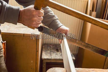 carpenter working on wood with frame