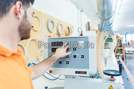 carpenter in furniture factory pressing button