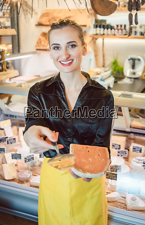 beautiful woman offering cheese on delicatessen