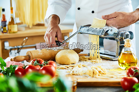 chef making noodles with kitchen in