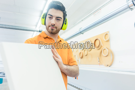 carpenter in furniture factory working on