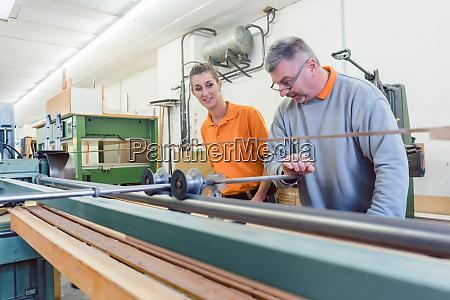 senior carpenter and female apprentice working