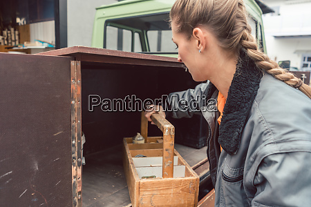 woman carpenter loading tools in mobile