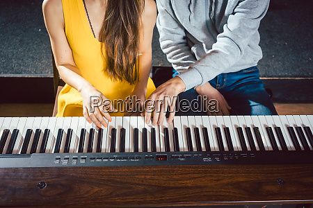 piano teacher giving music lessons to