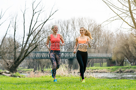 senior and young woman running as